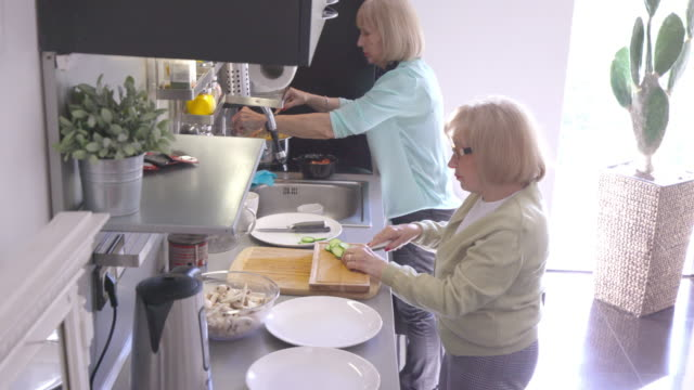 Senior women preparing lunch together by the stove
