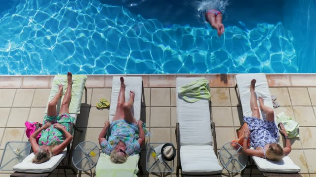 Senior Women Relaxing on Holiday Group of senior women relaxing by the poolside on holiday. Three women are lying down on their backs, sunbathing, while one woman dives into the swimming pool. swimwear stock videos & royalty-free footage