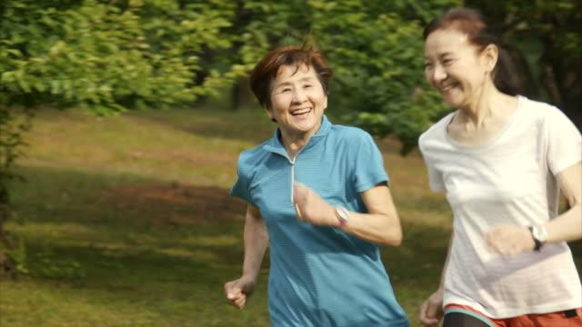 vidéos et rushes de femmes âgées jogging dans le parc yoyogi - seulement des japonais