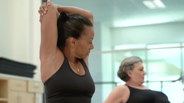 senior women stretching in fitness class - 60 69 anni video stock e b–roll