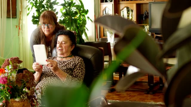 Senior women using digital tablet for video call with family