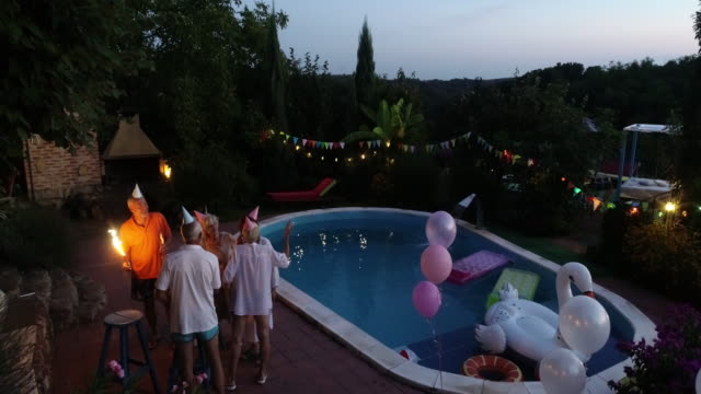 Seniors Birthday Party Group of senior friends celebrating birthday by the pool. pool party stock videos & royalty-free footage