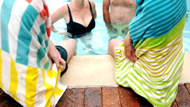 Seniors relaxing while interacting near poolside video