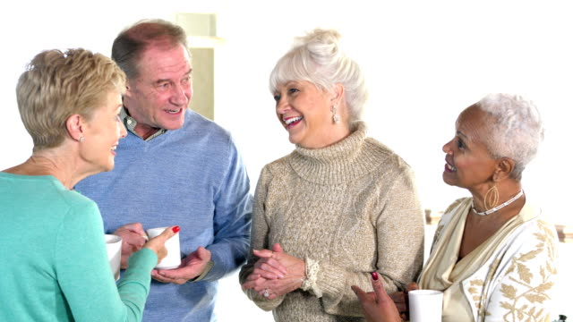 Seniors socializing, talking and laughing over coffee video