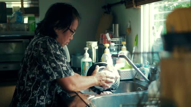 Seniors woman washing dishes at Home Mature woman washing dishes after breakfast in the kitchen. / Bangkok, Thailand. washing dishes stock videos & royalty-free footage