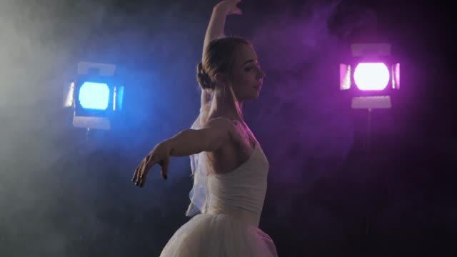 sensuell ballerina i vitt tutu dans element i klassisk eller modern balett, snurrar runt i mörkret med blått och violett ljus och rök på washers bakgrund - balettstång bildbanksvideor och videomaterial från bakom kulisserna