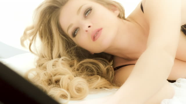 sensual blonde woman with wavy hair laying on bed - video