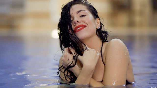 sensual brunette enjoys relaxation in swimming pool - rossetto rosso video stock e b–roll