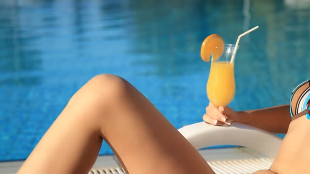 HD DOLLY: Sensual Woman Drinking Cocktail HD1080p: DOLLY shot of a young beautiful woman in bikini drinking cocktail while relaxing by the pool. 20 29 years stock videos & royalty-free footage
