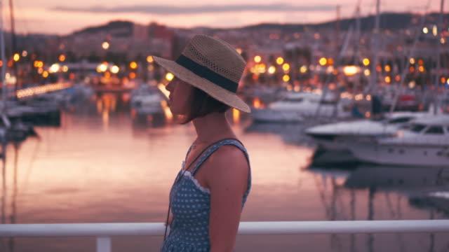 Sensual woman walking along quay at the sunset video