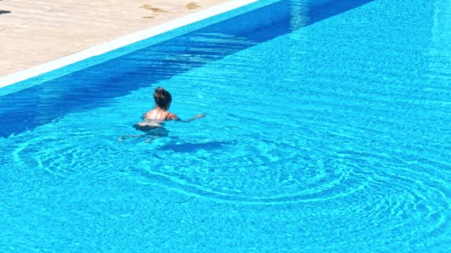 vídeos de stock e filmes b-roll de sensual young woman relaxing in swimming pool. - mulher natureza flores e piscina