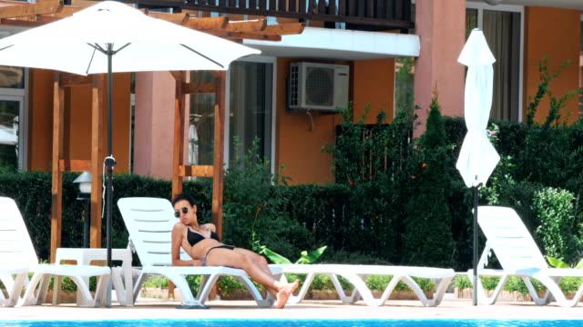 vídeos de stock e filmes b-roll de sensual young woman relaxing near swimming pool. - mulher natureza flores e piscina