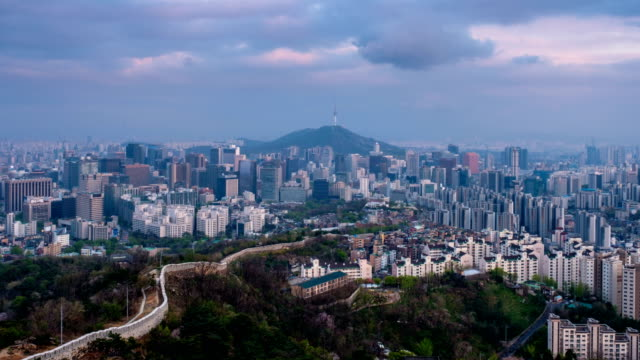 Seoul skyline on sunset timelapse, South Korea. Aerial timelapse of Seoul downtown cityscape and Namsan Seoul Tower from Inwang mountain with day to night transition. Seoul, South Korea. Zoom in effect seoul stock videos & royalty-free footage