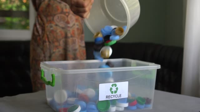 vídeos de stock e filmes b-roll de separate, sorting and recycle of the plastic bottle tops, caps and lids - box separate life