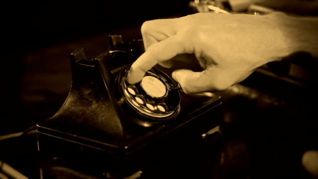 Sepia Dialing Old Phone A close up of a man dialing an old vintage 40's style desk telephone. Sepia tone applied for effect. Shallow depth of field. the past stock videos & royalty-free footage