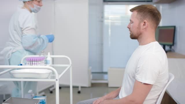 sequence of man receiving vaccination in hospital ward - flu shot стоковые видео и кадры b-roll