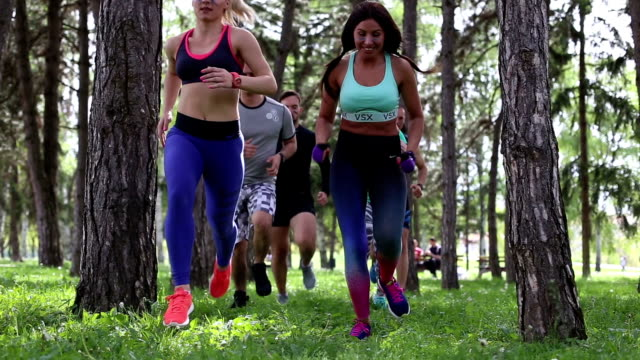 2 sequences - team of sport man and female running through trees in a park outdoors video