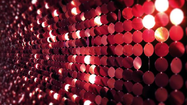 Sequins reflective background. Red, golden and blue. Sparkling.