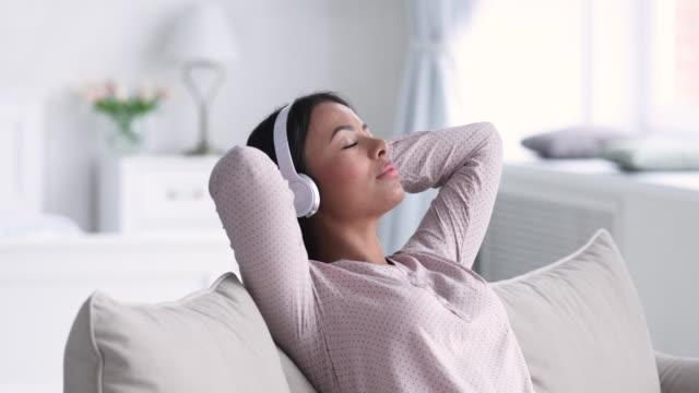 vídeos de stock, filmes e b-roll de mulher africana serena relaxando no sofá usar fones de ouvido ouvindo música - consciência negra
