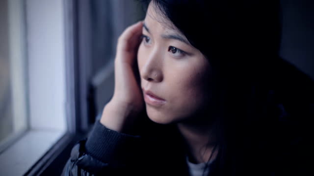 Serene Asian girl thinking while sitting near window.