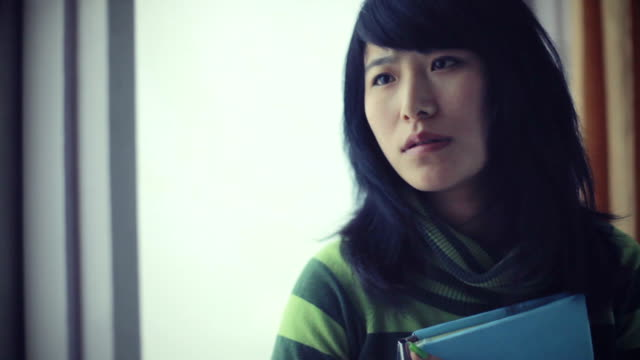 serene asian young adult student near window with book. - student life stock videos and b-roll footage