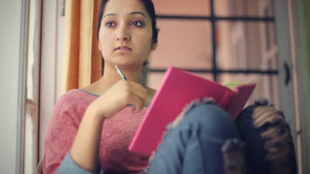Estudiante adulto joven asiática Serena junto a la ventana con el libro. - vídeo