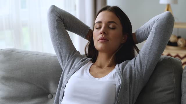 vídeos de stock, filmes e b-roll de mulher nova atrativa sereno que descansa no sofá que toma a respiração profunda - despreocupado