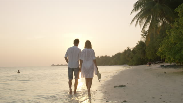 MS Serene couple holding hands,walking on tranquil tropical ocean beach at sunset,Maldives