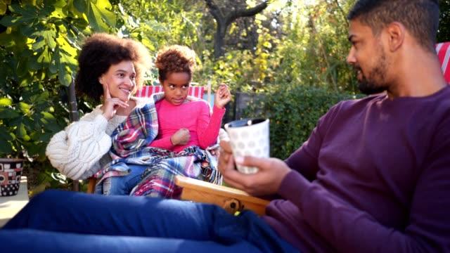 Serene family enjoying tea in a back yard