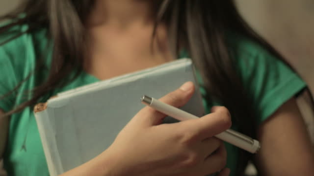 Serene girl looking at camera and holding a book. video