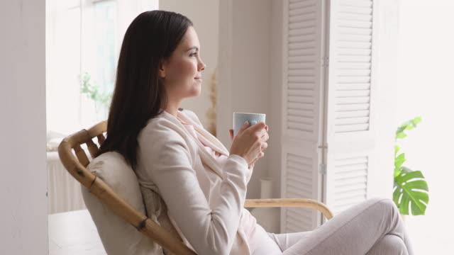 vídeos de stock, filmes e b-roll de mulher serena bebendo chá quente respirando ar fresco em casa - tea drinks