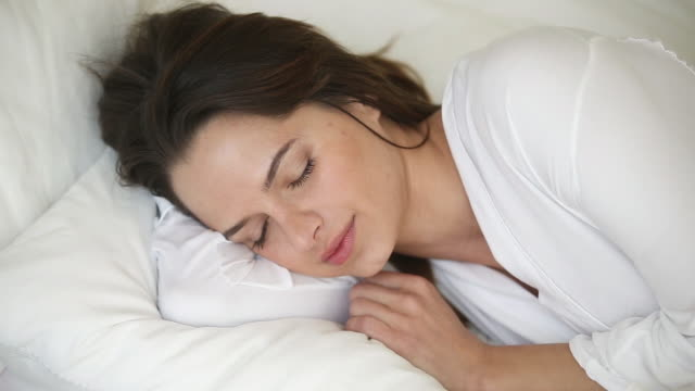 Serene woman lying on soft pillow in bed sleeping well