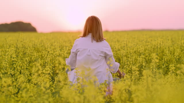 ms serene woman meditating,spinning in tranquil,rural oilseed rape field - mudra video stock e b–roll