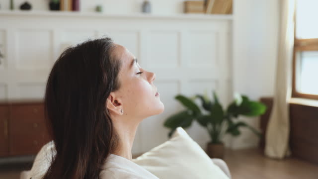Serene woman taking deep breath of fresh air at home Serene mindful pretty young woman taking deep breath of fresh air meditating with eyes closed at home. Calm lady doing yoga exercise feels no stress and life balance, peace of mind concept. Side view mental wellbeing stock videos & royalty-free footage