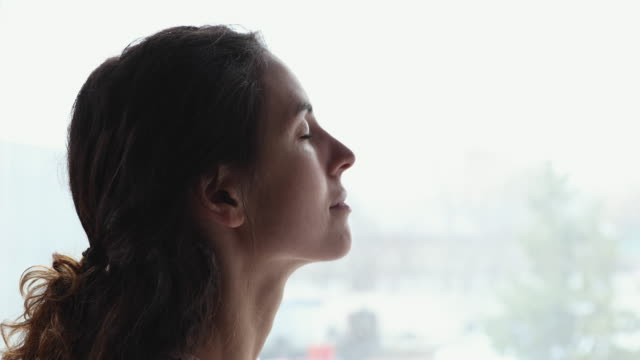 Serene young woman breathing fresh clean air with eyes closed Serene young woman breathing fresh clean air with eyes closed. Calm healthy adult lady feeling peace of mind, pleasure, tranquility, enjoying well being relaxing alone. Profile side face close up view mental wellbeing stock videos & royalty-free footage