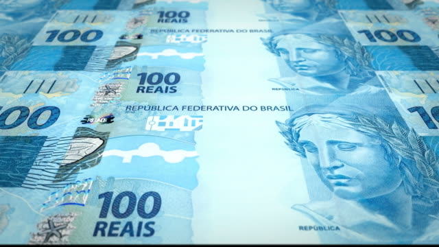 Series of banknotes of one hundred brazilian reals of the bank of Brazil rolling on screen, coins of the world, cash money, loop video
