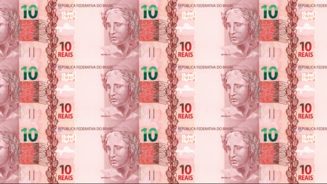 Series of banknotes of ten brazilian reals of the bank of Brazil rolling on screen, coins of the world, cash money, loop video