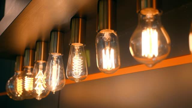 vídeos de stock, filmes e b-roll de uma série de lâmpadas de poupança de energia modernas de incandescência no estilo retro é vendida no st - led