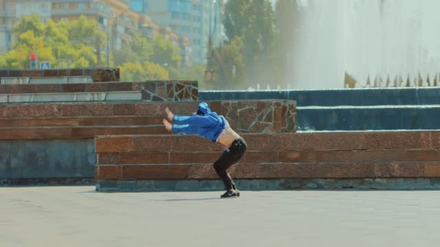 Series of somersaults at the fountain in the park. Parkour on a city street.