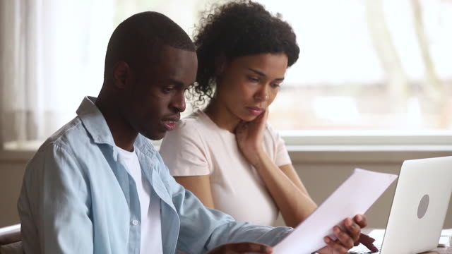Serious african american couple doing paperwork use laptop together