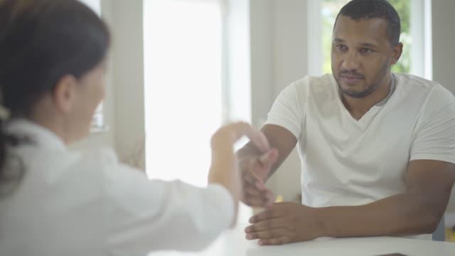 grave uomo afroamericano che stringe la mano alla donna caucasica in ospedale. ritratto del paziente su consulenza medica in ospedale. medico donna consulente cliente in clinica. - fragilità video stock e b–roll