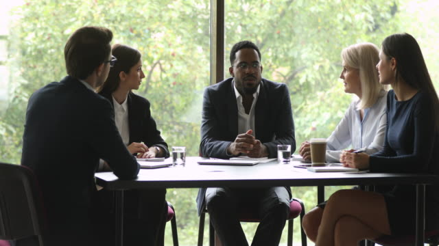 Serious african american team leader in eyeglasses holding business meeting.