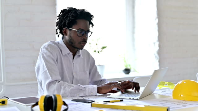 serious african architecture engineer working on laptop in office - drawing activity stock videos & royalty-free footage