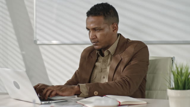 Serious African businessman working on laptop in modern office video