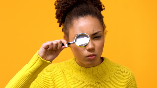 Serious african woman looking through magnifying glass, female detective, search Serious african woman looking through magnifying glass, female detective, search magnifying glass stock videos & royalty-free footage