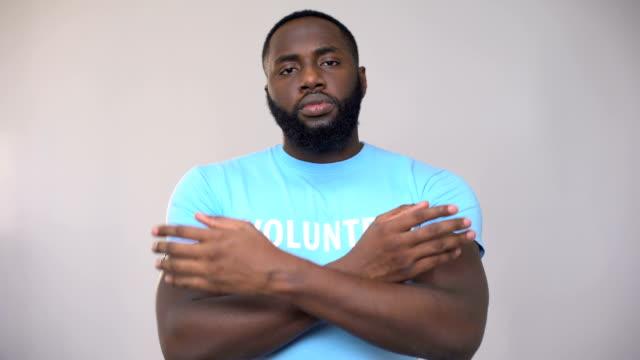 vídeos de stock, filmes e b-roll de pé voluntário afro-americano sério com mãos cruzadas, atividade altruísta - consciência negra