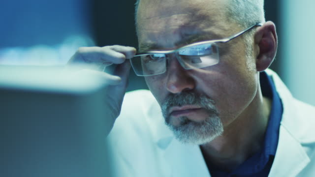 Serious and Focused Scientist Working on Computer.  Shot on RED Cinema Camera in 4K (UHD). Serious and Focused Scientist Working on Computer. Shot on RED Cinema Camera in 4K (UHD). lab coat stock videos & royalty-free footage