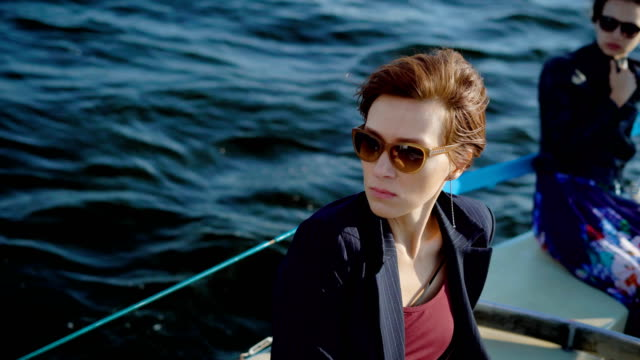 serious and thoughtful dark-haired women are wearing sunglasses are sitting on a board of boat in sunny day video