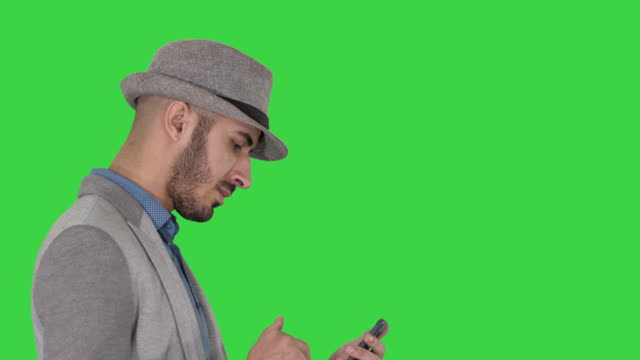 Serious arabic casual man using smartphone while walking on a Green Screen, Chroma Key