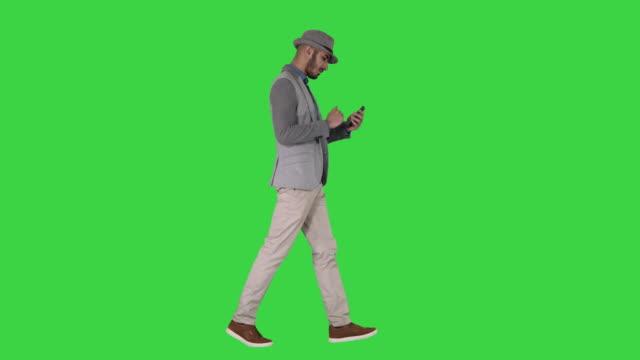 グリーンスクリーン、クロマキーを歩きながらスマートフォンを使用して深刻なアラビアのカジュアルな男 - 全身点の映像素材/bロール